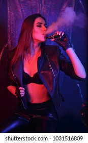 Young pretty woman smoking e-fag wearing black leather jacket. Sexy girl exhales a thick white smoke.smoking fruit flavored e-liquid or e-juice with vaporizer device or e-cig.Modern gadget for smokers