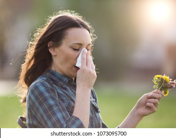 Young pretty woman sneezing and blowing nose while holding bouquet of spring flowers from meadow. Pollen allergy symptoms