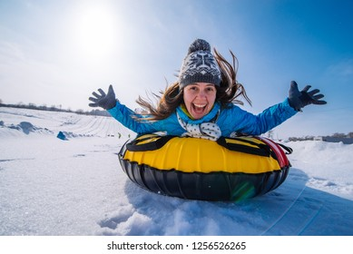 young pretty woman at snow tubing rise hands up. slide from snow hill. winter activity