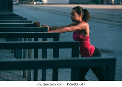 Young pretty woman in sporty clothes standing outdoors with hands on the banister