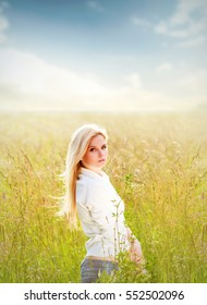 Young pretty woman standing in field in sunny day