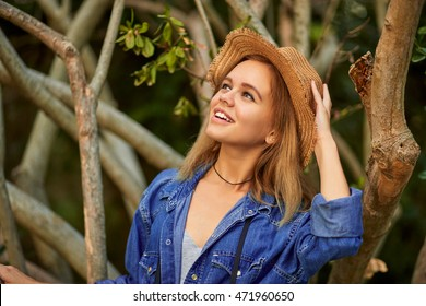 Young pretty woman standing in the tropical forest, touching an unusual tree. Wearing denim shirt and stylish light hat. Happy smiling girl.
