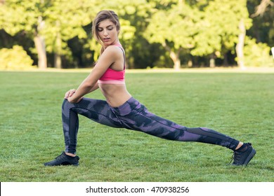 Young pretty woman stretching in the park before a run