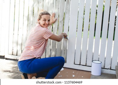 young, pretty woman strokes the garden fence with white paint in summer