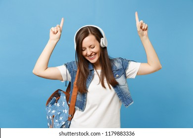 Young pretty woman student with closed eyes with backpack, headphones listen music pointing index finger up dancing isolated on blue background. Education in high school. Copy space for advertisement