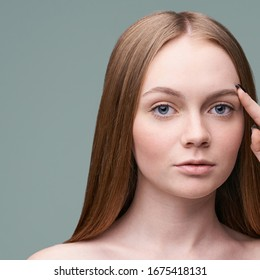 Young pretty woman studio portrait. Cosmetology concept. Esthetic woman face. Skin care dermatology beauty contour. Harmony girl. For cream, lotion square banner. Point at eye. Copyspace