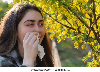 A young pretty woman is suffering from allergies. Red eyes and running snot. The concept of seasonal allergies and colds. Close up.