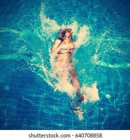 Young pretty woman in swimsuit jumping into the pool with a splash. Toned