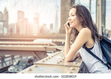 Young pretty woman talking at cellular phone on Brooklyn Bridge - Mixed race woman having a conversation at smartphone, city at sunset in the background
