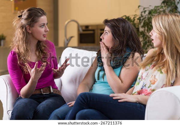 Young pretty woman telling the fascinating story to her girlfriends
