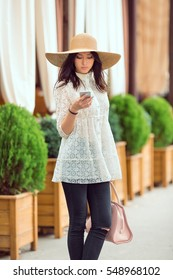 Young pretty woman texting outdoors. Beautiful young stylish asian girl in white dress and hat with phone and handbag against cofe city background. Casual stylish look model