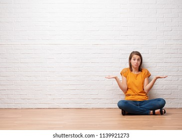 young pretty woman thinking or looking pensive to an empty place against brick wall background