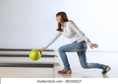 Young pretty woman throwing a bowling ball