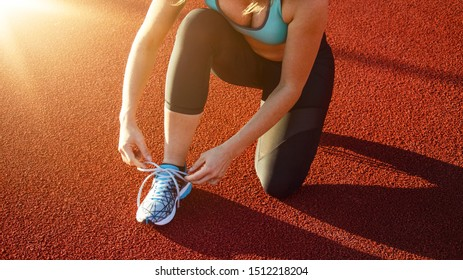 young pretty woman ties her sport shoes before she starts to run on a hard ground