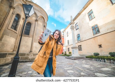 young pretty woman tourist taking slefie in old street in europian city