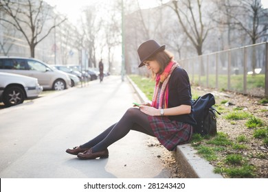 young pretty woman in town using smartphone