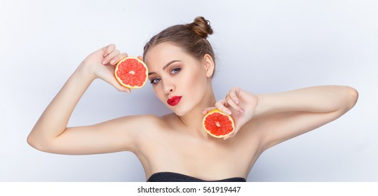 Young pretty woman trendy makeup bright red lips bun hairstyle bare shoulders act the ape with grapefruits white studio background