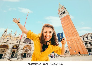 young pretty woman with ukrainian biometric passport at main venice square