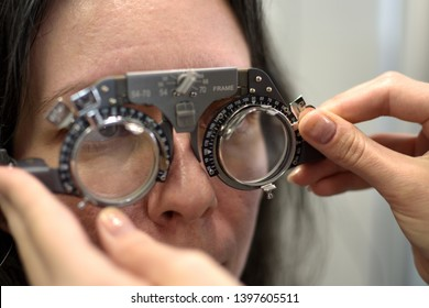 young pretty woman undergone lens fitting procedure in vintage style lens testing matching frame with ophthalmologist optometrist optician, low depth of field