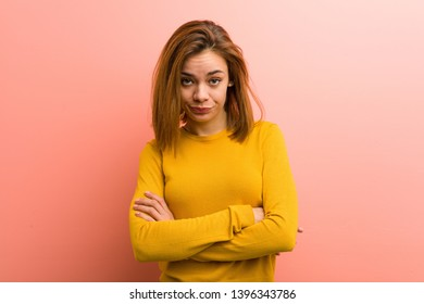 Young pretty young woman unhappy looking in camera with sarcastic expression.