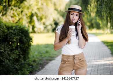 Young pretty woman using phone and drink coffee walking in summer park.