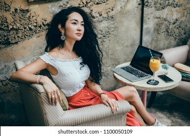 Young pretty woman using smartphone and laptop in cafe,drink coffee in cup, sweet breakfast, happy face, outdoor hipster portrait, fashion girl, table, smoothie, healthy food, hipster cafe, crazy face