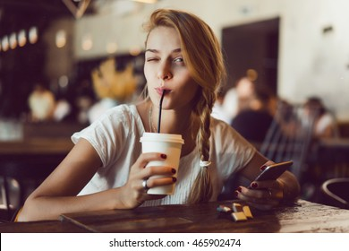 Young pretty woman using smartphone in cafe, drink coffee in cup, sweet breakfast, happy face, outdoor hipster portrait, fashion girl, table, smoothie, healthy food, hipster cafe, crazy face