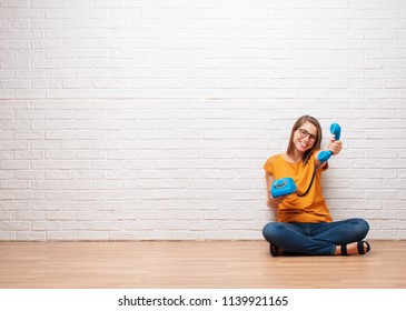 young pretty woman with a vintage telephone sitting on a wooden floor against brick wall texture.