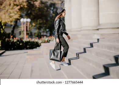 Young pretty woman walking up the stairs in the city