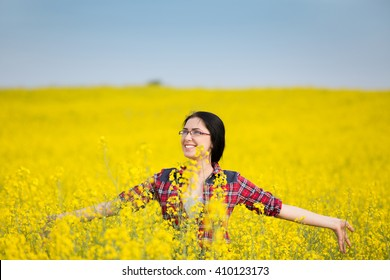 Young pretty woman walking through yellow blossom rapeseed field with spread arms. Enjoyment and freedom outdoor concept
