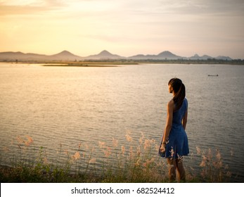 young pretty woman wearing summer dress  on the nature near river  and  sunset