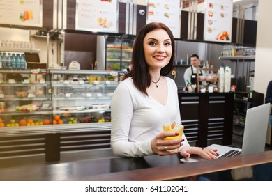 Young pretty woman in a white blouse sits at a table and use her laptop in a cafe