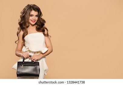 Young pretty woman in white dress holding black handbag. Yellow background.
