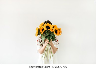 Young pretty woman in white dress hold sunflowers bouquet on white background. Floral minimal composition.