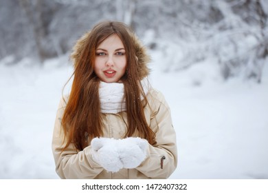 Young, pretty woman in a white knitted scarf and a beige down jacket with long hair breathes on snowflakes in the open air in a snowy forest. Youth, beauty, healthy lifestyle, dreams.