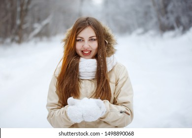 Young, pretty woman in a white knitted scarf and a beige down jacket with long hair throws up snowflakes in the fresh air in a snowy forest. Youth, beauty, healthy lifestyle, dreams.