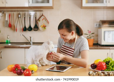 The young pretty woman with white persian cat in the kitchen with tablet on the table. Vegetable salad. Dieting concept. Healthy lifestyle. Cooking at home. Prepare food.