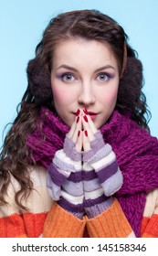 Young pretty woman in winter dress on blue background