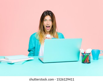 young pretty woman working with a laptop feeling shocked, astonished and surprised, with hand on chest and open mouth, saying who, me?