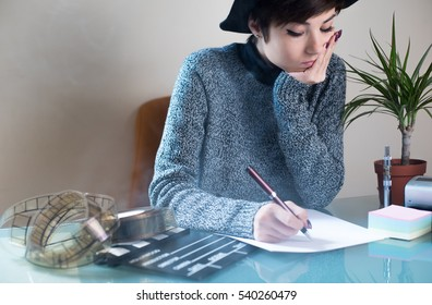 Young pretty woman writing on desktop with movie objects, clapper and filmstrip, with cigarette smoke in the air