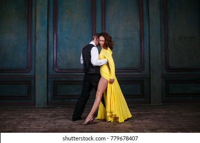 Young pretty woman in yellow dress and man dance waltz