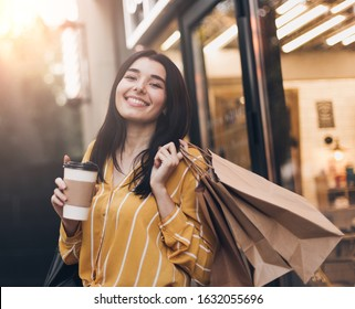 Young pretty woman in yellow skirt with shopping bags, cup of black coffee and smartphone