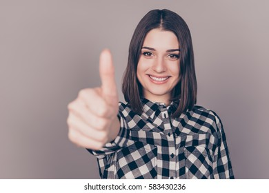 Young pretty women showing thumb up gesture against gray background