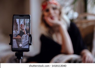 Young pretty women takes pictures of himself remotely, using selfie stick, poses in studio. Moroccan Studio Room