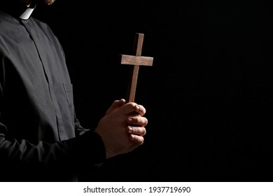 Young priest praying to God on dark background - Shutterstock ID 1937719690