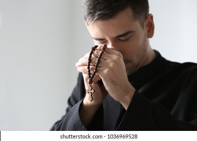Young priest with rosary beads praying on light background