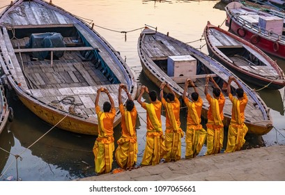 Young priests offer prayers to the Ganges river at sunrise as part of a ritual ceremony at Varanasi, India.