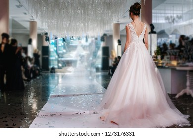A young princess in an expensive, luxurious dress with a long train stands with her back to the camera. Stylish Fashion. Bride in wedding day. Woman walk the runway during a Fashion Show.