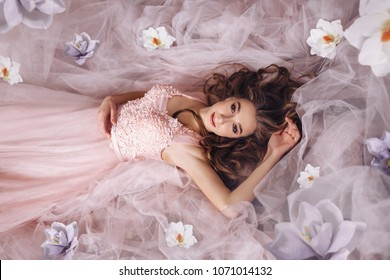A young princess with long fair-haired hair in a sumptuous pink dress lies on the floor, on a train, in fabrics, tender flowers are scattered around her. Girl spring. Artistic Photography