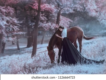 A young princess in a vintage dress with a long train, with tenderness and love, hugs her horse. The brunette girl in a white blouse, black skirt. The background is fantastically beautiful forest